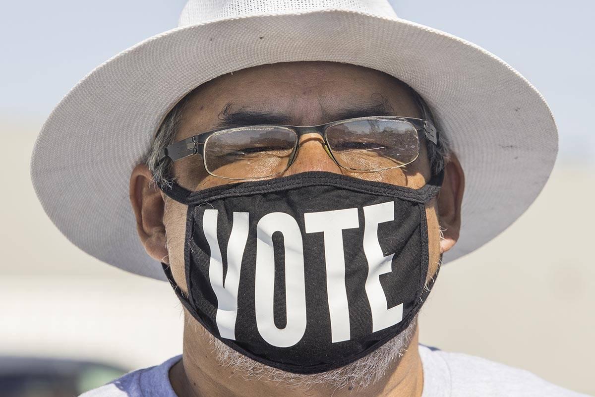 """Eddie Ramos lleva un cubrebocas con la palabra """"vota"""" antes de que la candidata demócrata a la ..."""