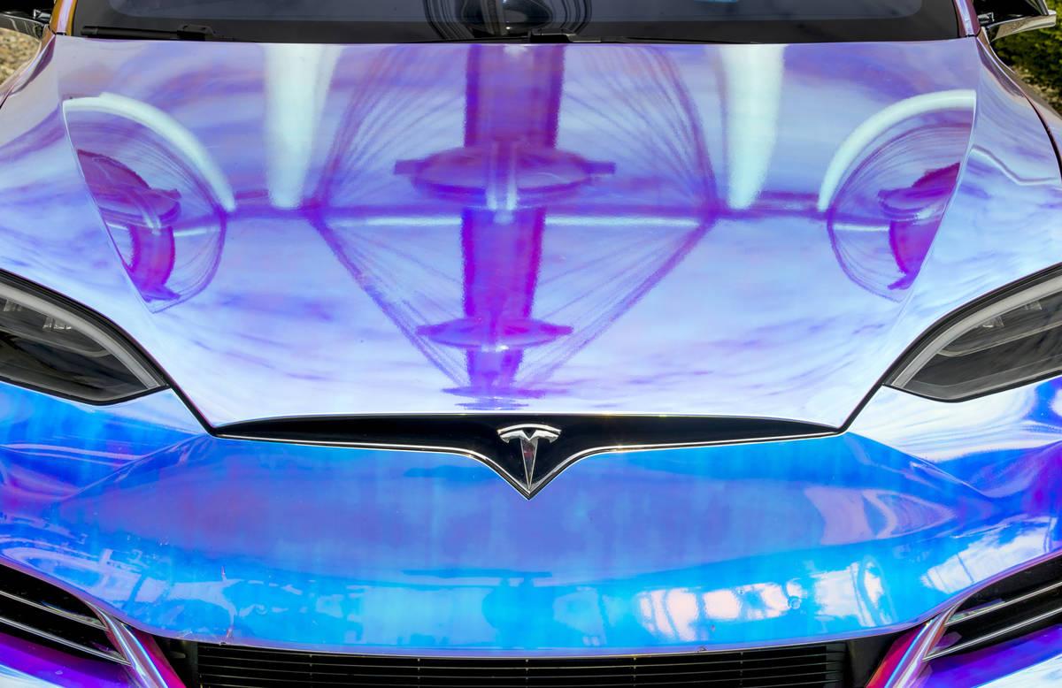 The High Roller se refleja en el cofre de un Tesla estacionado en la estación de supercarga de ...