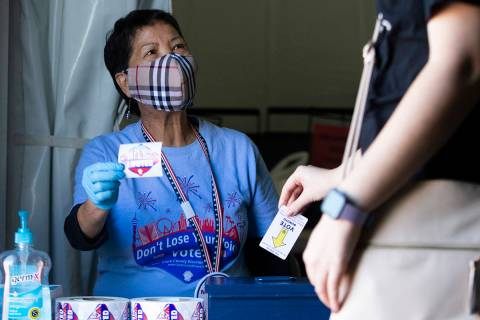 Wilma Dal Mundo, quien ha sido trabajadora electoral por 13 años, reparte calcomanías con la ...
