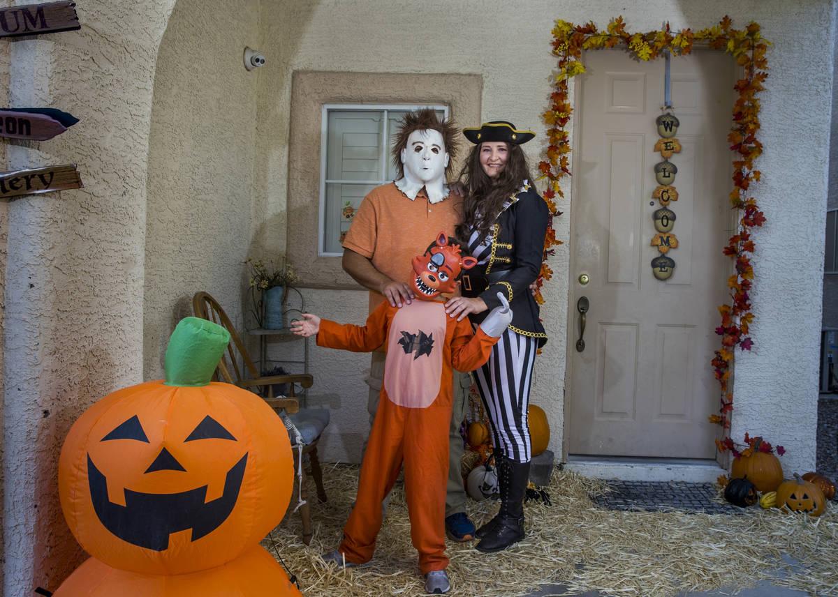 Alex Montenegro, de ocho años, con sus padres Joe y Kim Cabrero disfrazados en su casa decorad ...