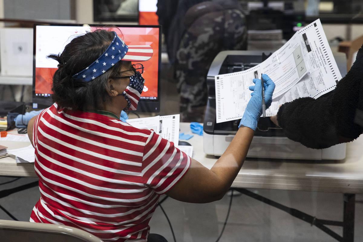 Una trabajadora electoral del Condado Clark revisa una boleta mientras se prepara para escanear ...
