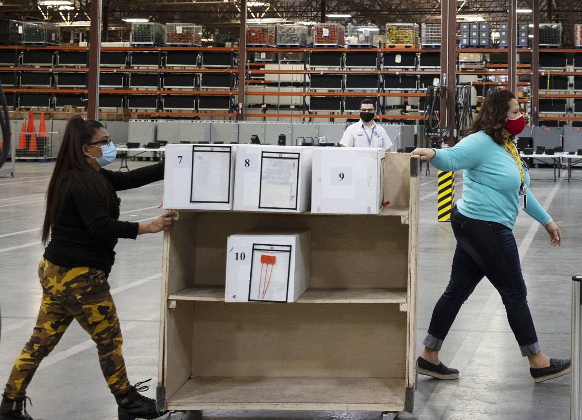 Trabajadores electorales del Condado Clark entregan las boletas para ser contadas en el almacé ...