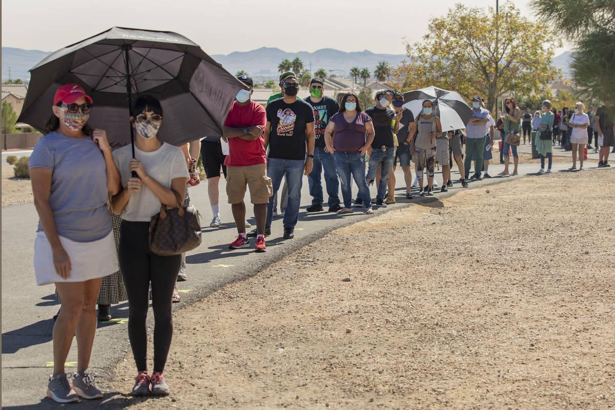 Gente se alinea para votar en la tienda de eventos ubicada en el centro de votación del Desert ...