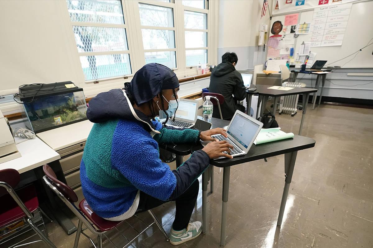 Los estudiantes Kenny Scottborough, izquierda, y Tai Nguyen trabajan en sus computadoras comple ...