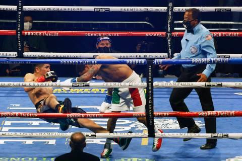 Gervonta Davis, derecha, empuja a Leo Santa Cruz hacia abajo durante una pelea de box el sábad ...
