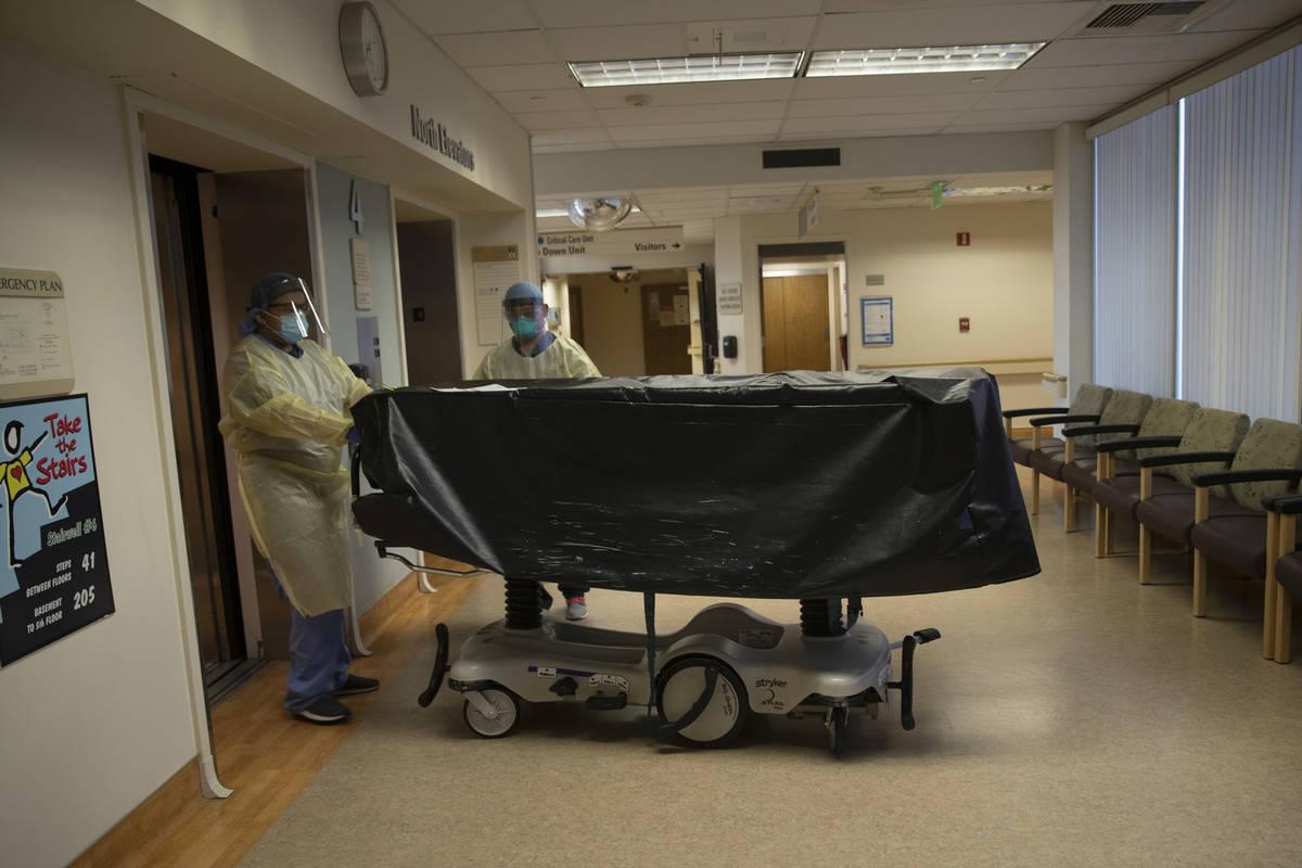 Miembros del personal del hospital entran en un ascensor con el cuerpo de una víctima de COVID ...