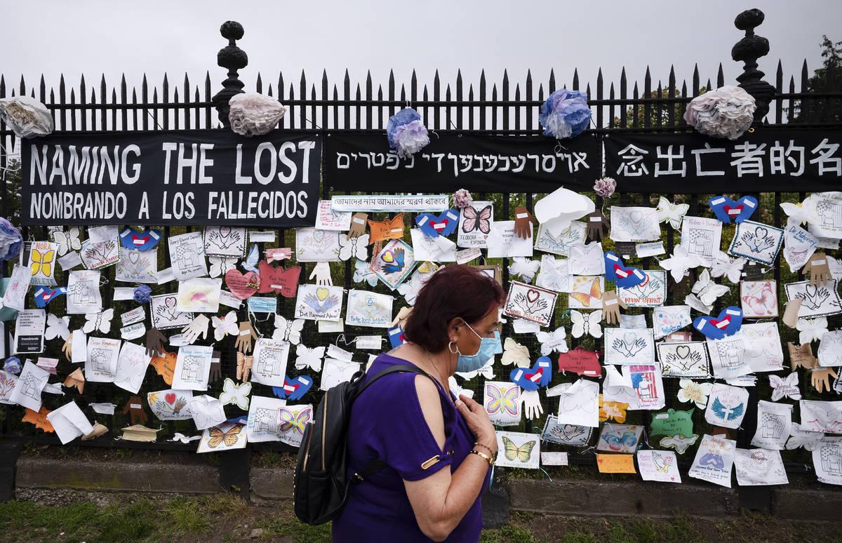 Una mujer pasa por una valla en las afueras del cementerio Green-Wood de Brooklyn, adornada con ...