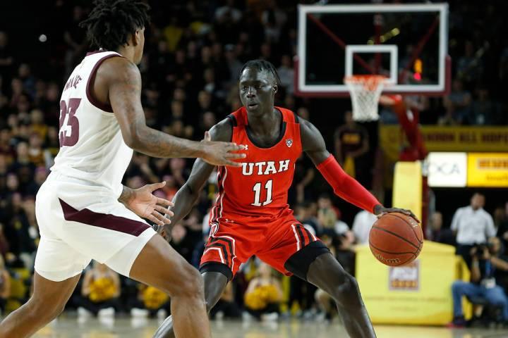 ARCHIVO - El escolta de Utah Both Gach (11) avanza el balón en la cancha mientras Romello Whit ...