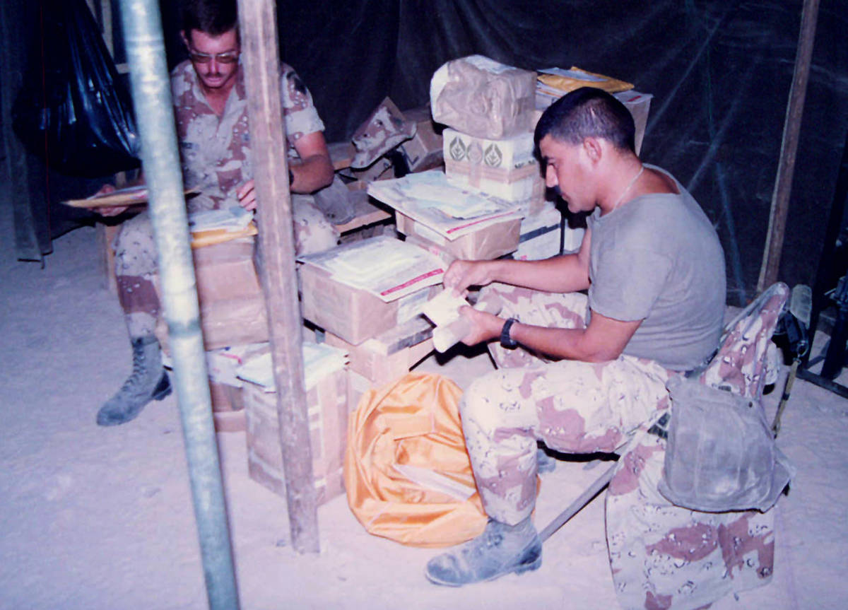 First Sergeant Alfred Ferryerra sorts stacks of mail sent to soldiers at the start of Desert Sh ...