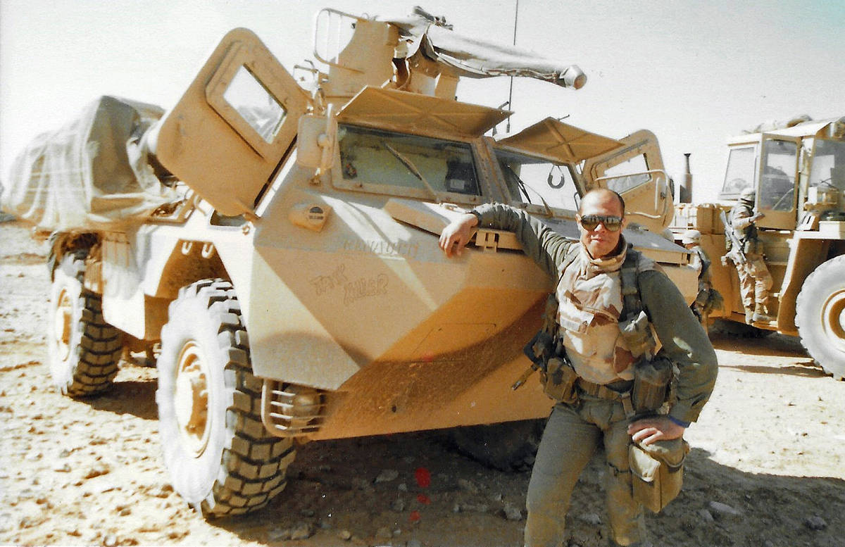 A French Soldier proudly poses with his light armored vehicle and its 25mm Bushmaster main gun ...