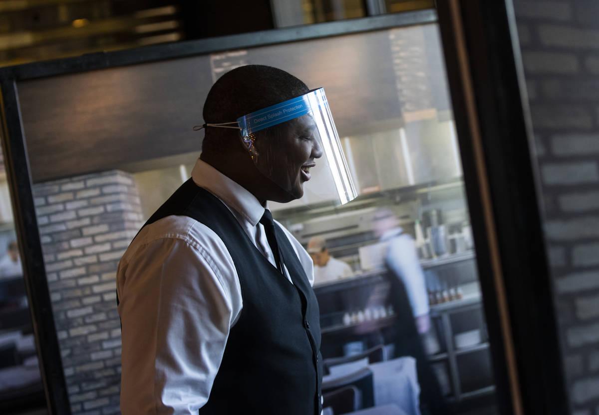 Donald Bailey usa un protector facial mientras sirve a los comensales en Nora's Italian Cuisine ...