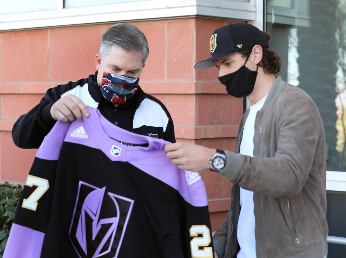 Jon Bilstein, director ejecutivo de Comprehensive Cancer Centers, izquierda, recibe una jersey ...