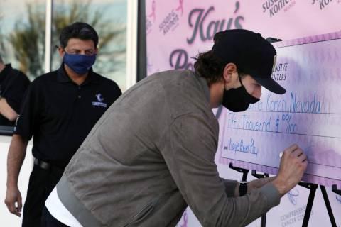 El defensa de los Golden Knights, Shea Theodore, firma un cheque de 50 mil dólares con el doct ...