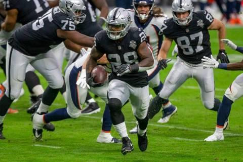 El jugador de Las Vegas Raiders, Josh Jacobs (28), corre con el balón contra los Broncos de De ...