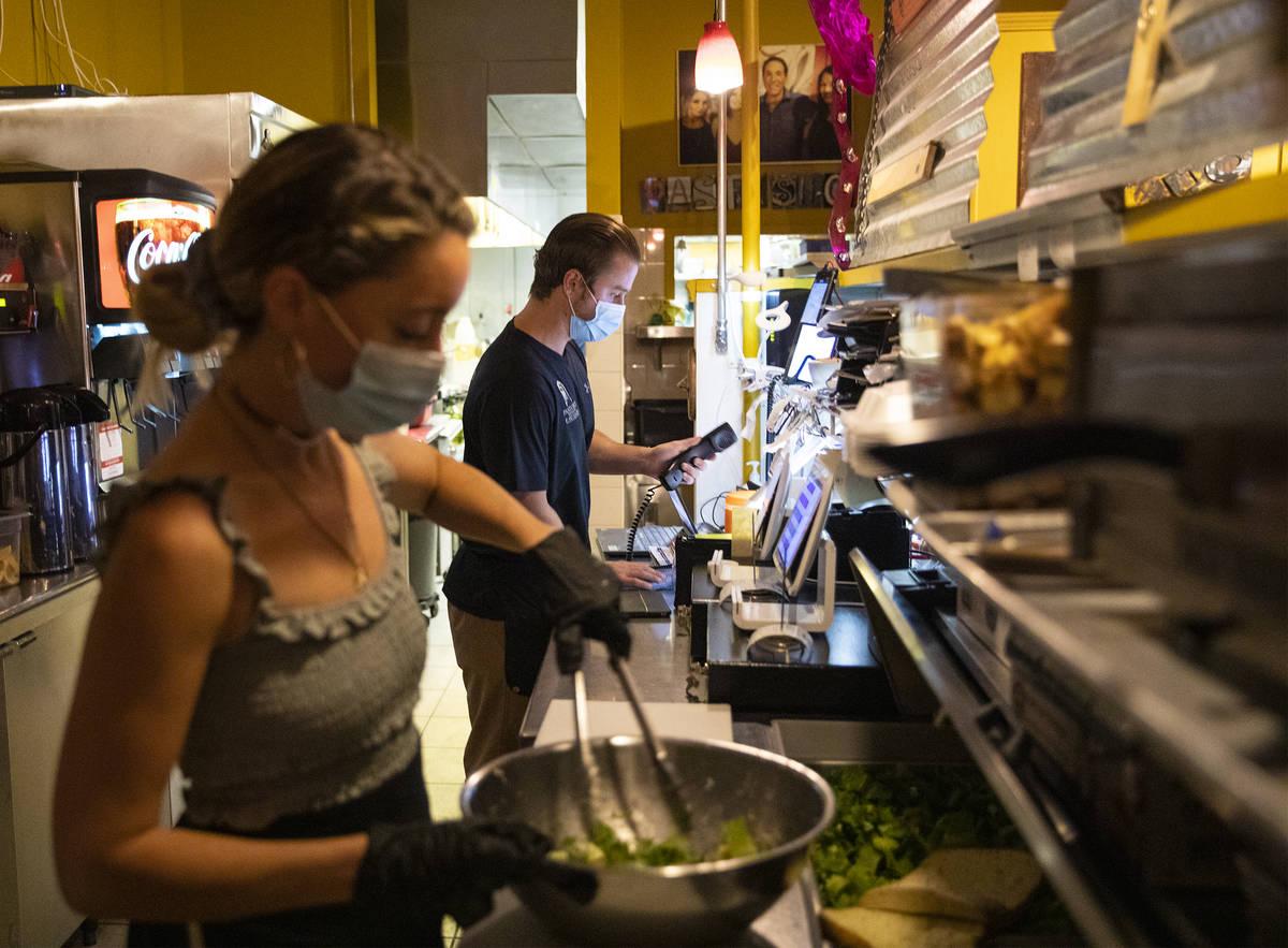 Bianca Alenik, izquierda, prepara una ensalada mientras Dakota Wadkins, derecha, toma un pedido ...
