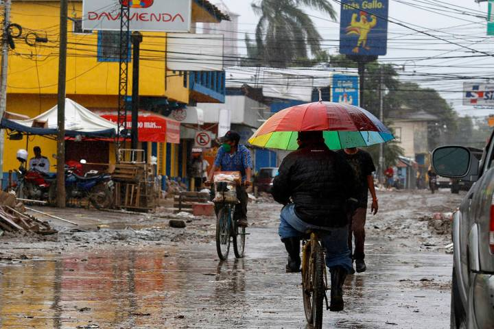 Los lugareños se mueven en la calle apenas despejada de los escombros de la última tormenta, ...