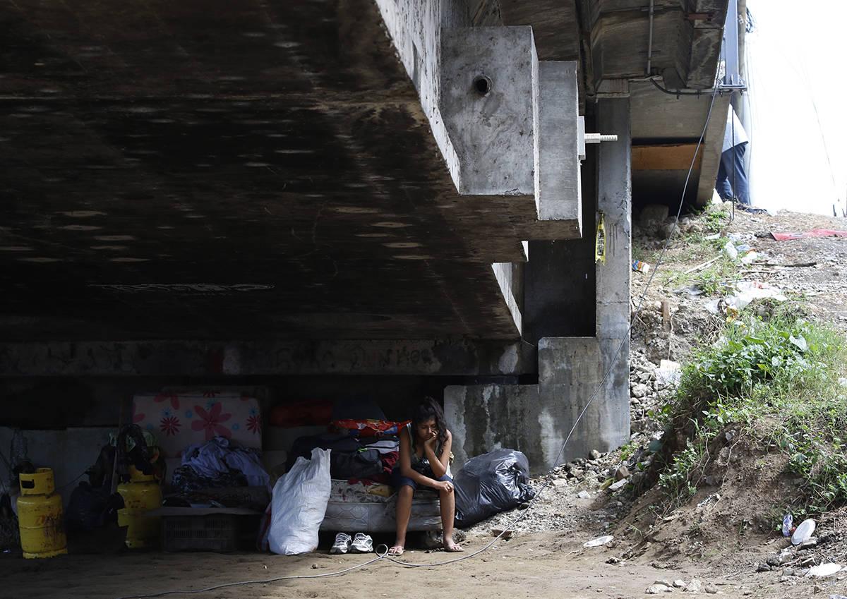 Mileydi Duarte, quien fue evacuada hoy por su familia, descansa debajo de un puente de la carre ...