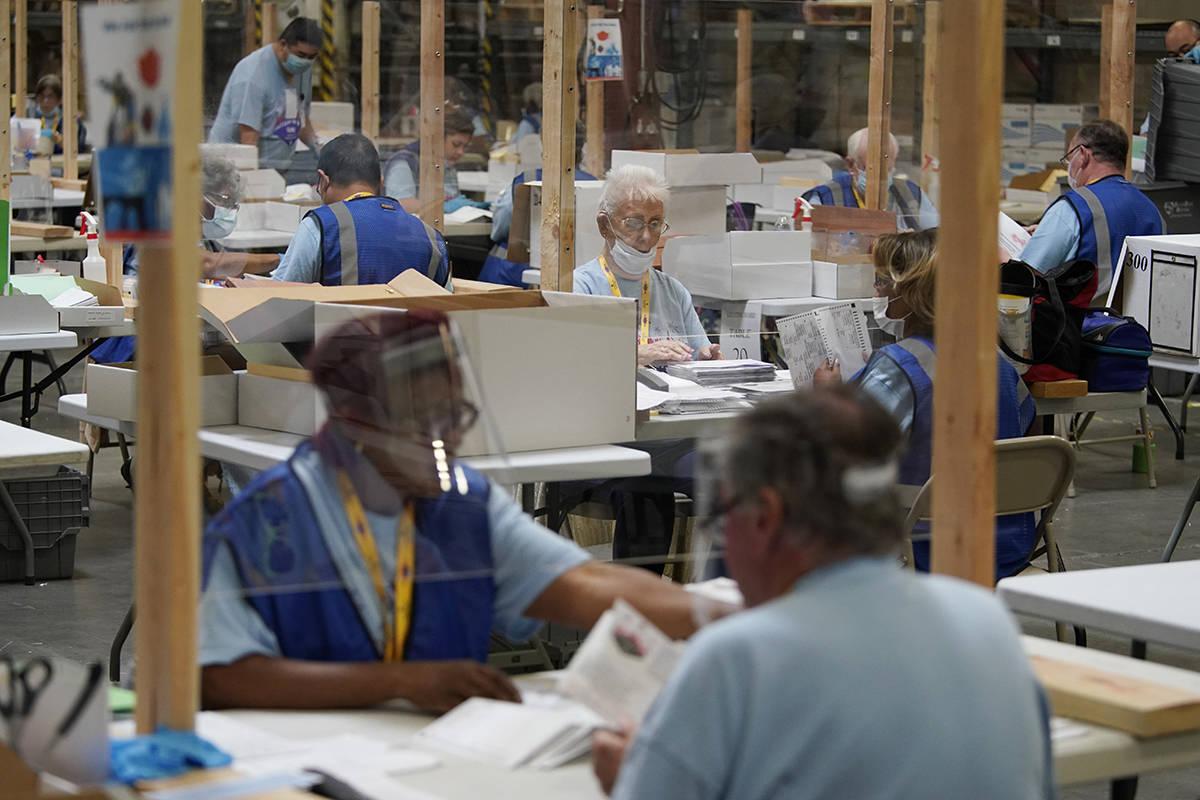 Trabajadores electorales procesan las boletas por correo durante una elección primaria casi ex ...