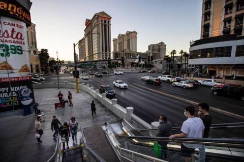 La gente toma una escalera mecánica a un puente peatonal sobre Flamingo Road en Las Vegas Stri ...