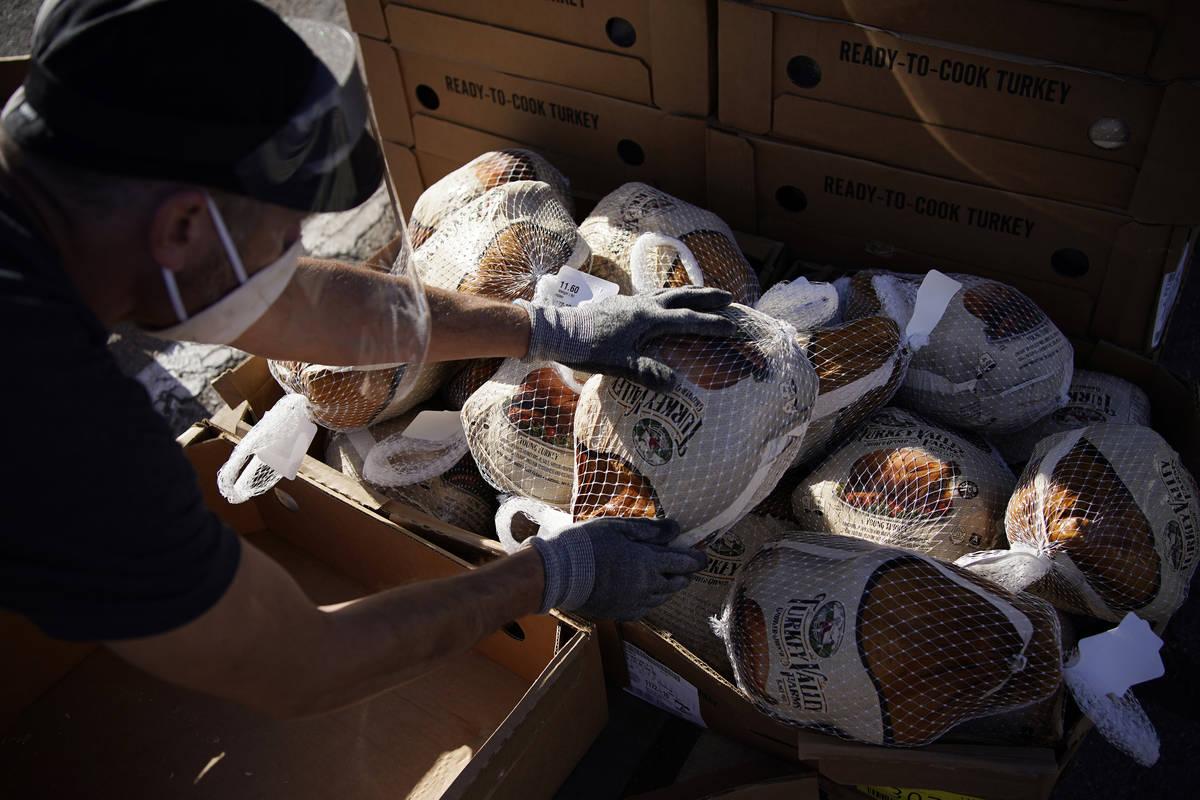 Un voluntario desempaqueta pavos congelados para regalarlos en un evento de distribución de co ...