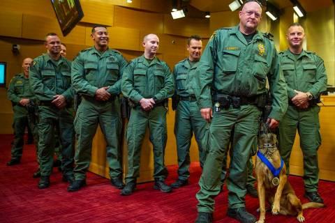 El oficial K-9 de la policía de Las Vegas, Jeff Corbett, con su perro Hunter, son flanqueados ...