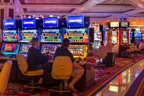Jugadores de tragamonedas en Wynn Las Vegas se sientan uno al lado del otro mientras el goberna ...