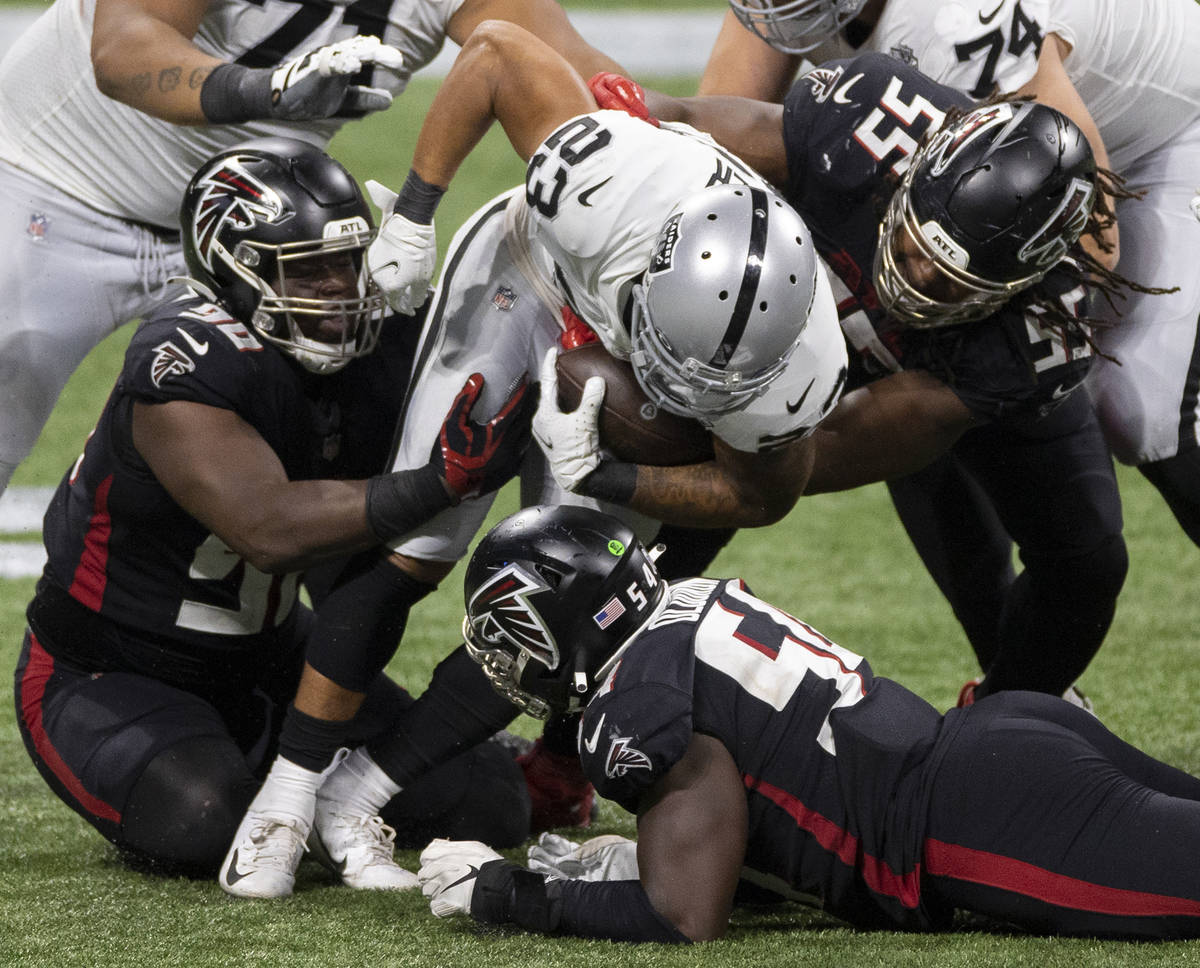 El running back Devontae Booker (23) de los Atlanta Falcons es abordado por el tackle defensivo ...