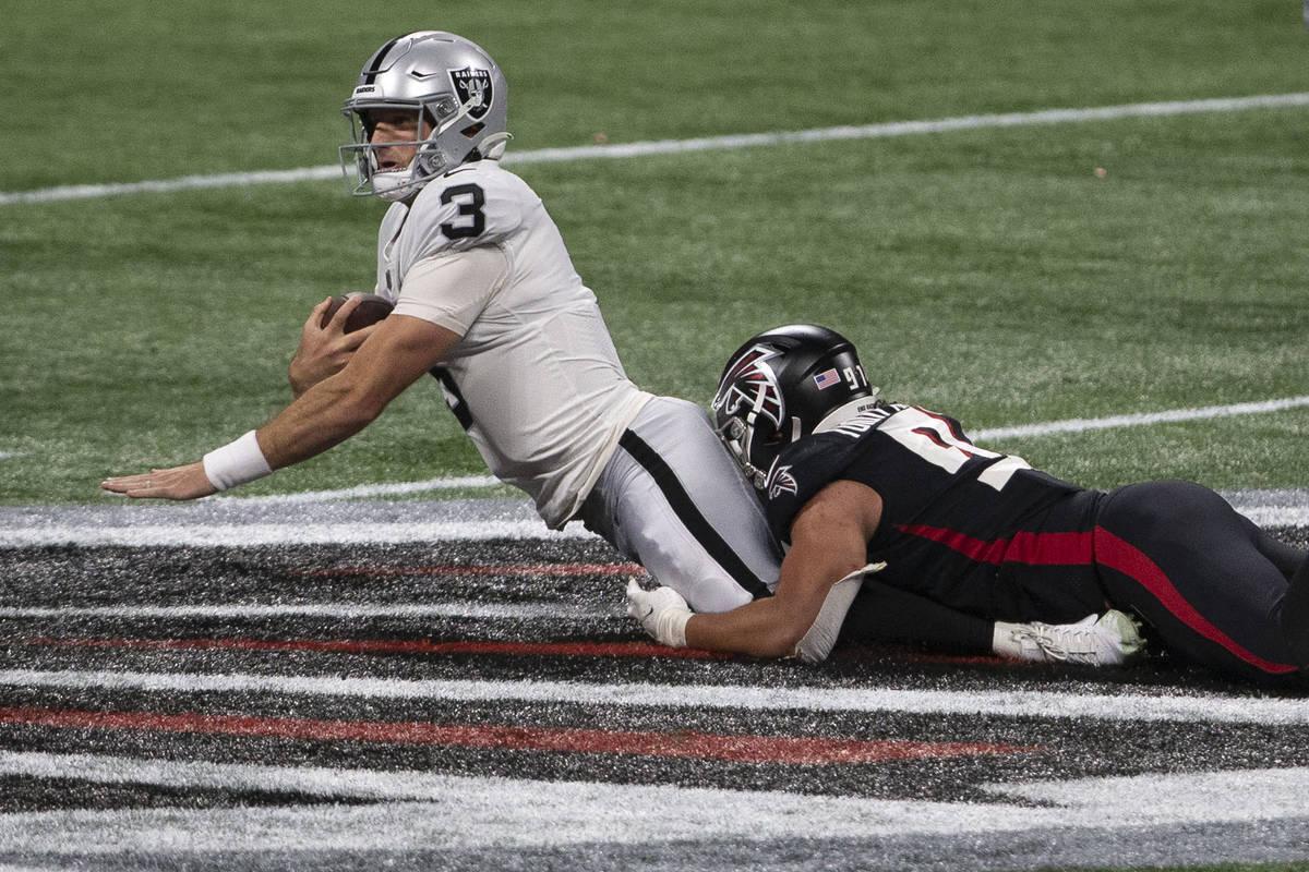 El mariscal de campo de los Raiders de Las Vegas, Nathan Peterman (3), es abordado por el tackl ...