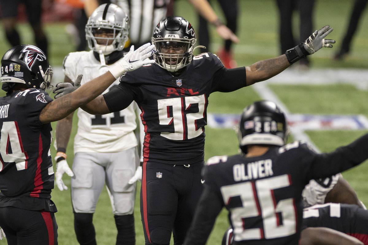 El cornerback de los Atlanta Falcons, Darqueze Dennard (34), el extremo defensivo, Charles Harr ...