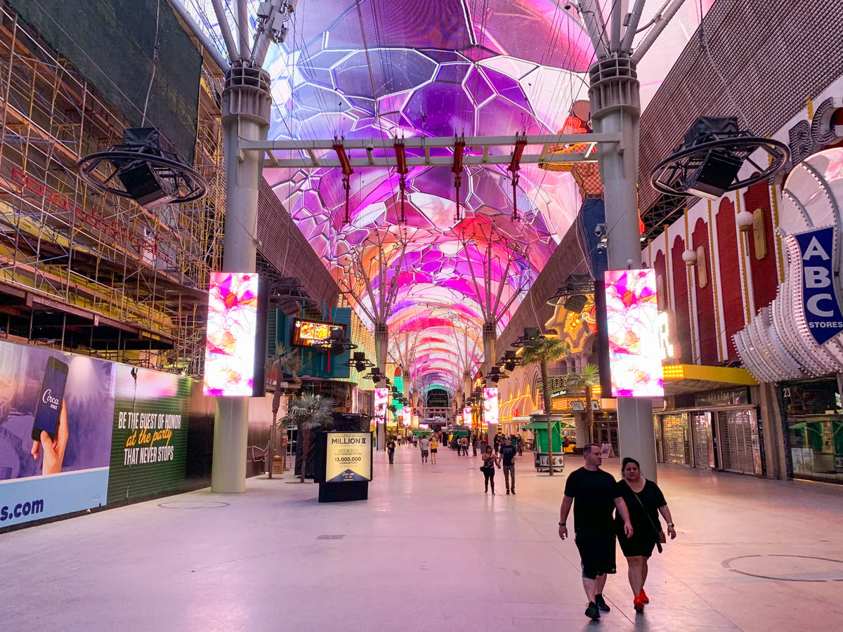 Gente camina por Fremont Street Experience después de que los casinos reabrieran en el centro ...