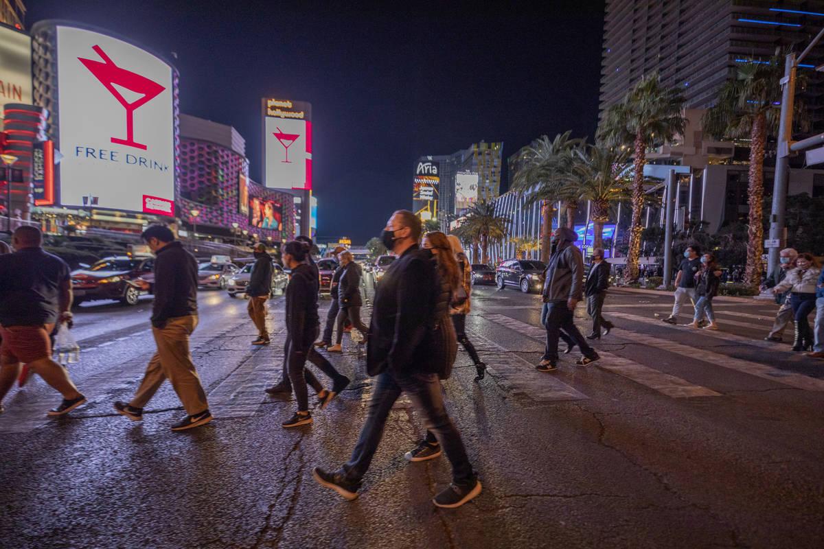 Tourists walk across Las Vegas Blvd., on the Strip, Friday, Nov. 27, 2020, in Las Vegas. (Eliza ...