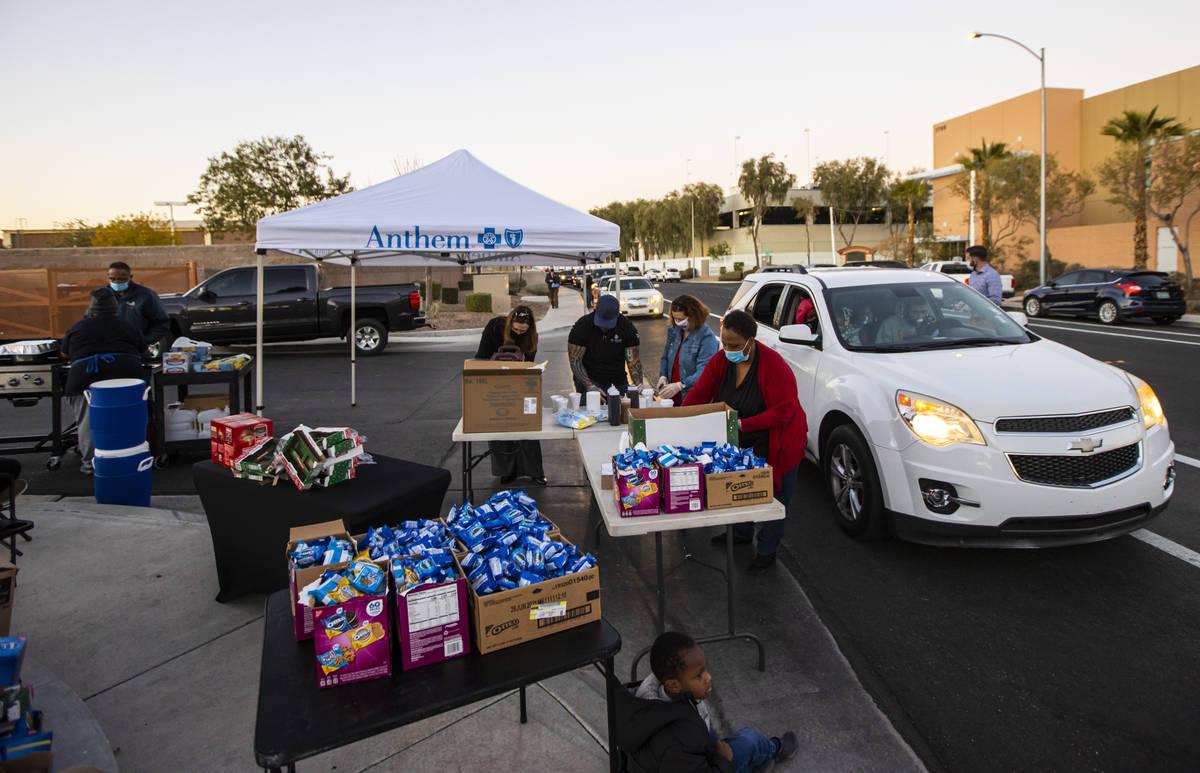 Kisha Walker, una voluntaria de Liberty Baptist Church, al centro, prepara comida y bocadillos ...