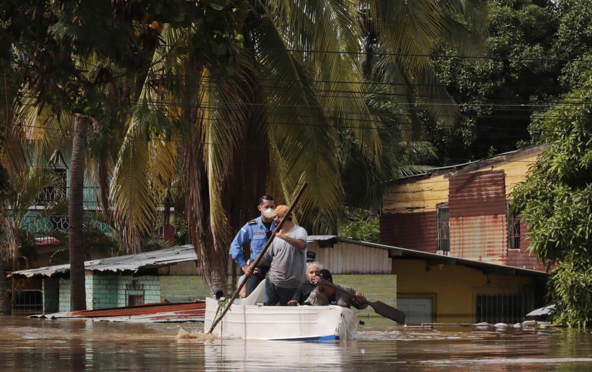 Residentes reman un bote a través de una calle inundada tras el huracán Eta en Planeta, Hondu ...