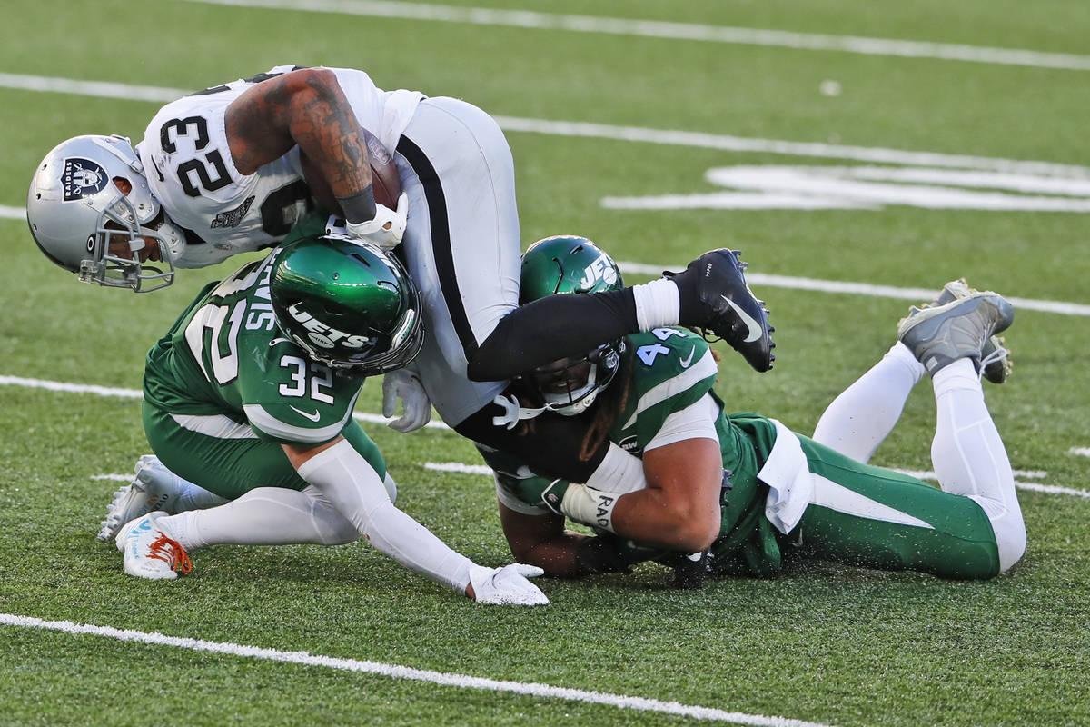 Devontae Booker de los Raiders de Las Vegas (23), arriba, intenta escapar de los defensores de ...