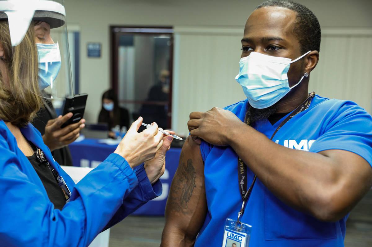 La enfermera de salud del University Medical Center, Lori Conti, administra una vacuna contra C ...