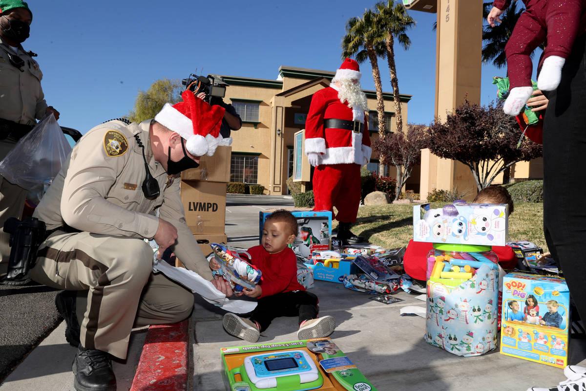 El oficial de policía de Las Vegas, Mike Sian, observa a Adriel Stephens, de un año, abrir re ...