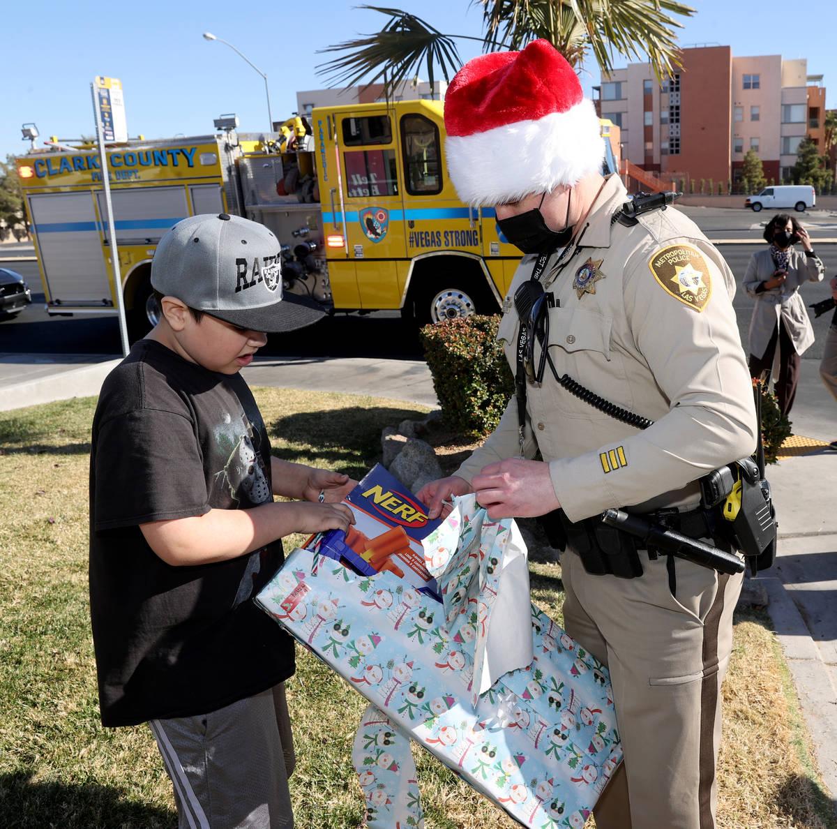Josh Irwin ayuda a Kevin Salazar, de ocho años, a abrir un regalo durante la caravana de jugue ...