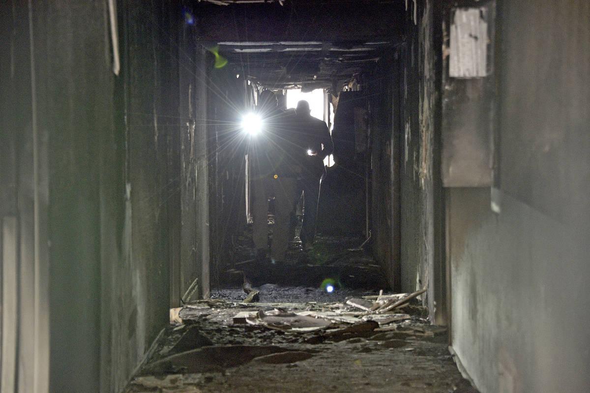 Investigadores caminan por un corredor interior el 21 de diciembre de 2019 después de un incen ...