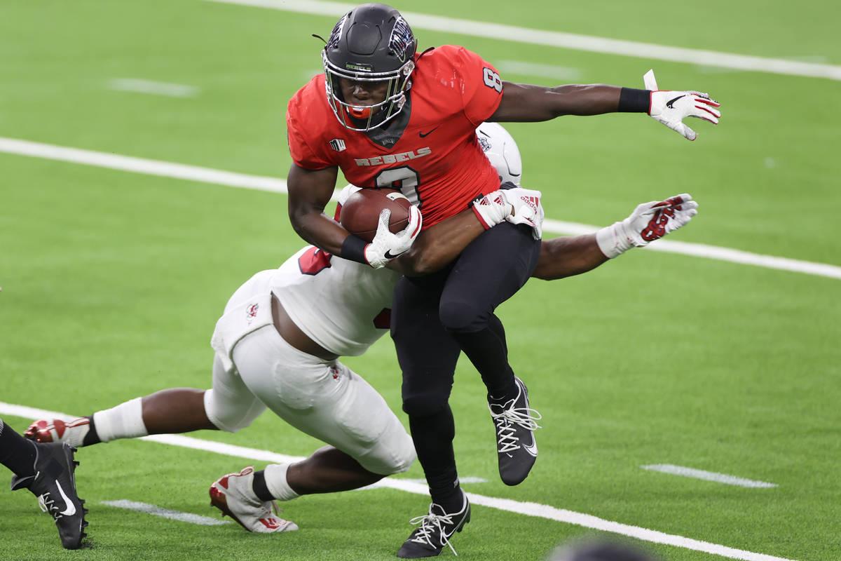 El running back de los UNLV Rebels, Charles Williams (8), es tacleado por el linebacker de los ...