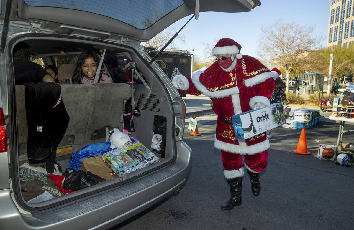 "Santa Claus carga regalos durante el primer evento ""NLVPD Holiday Toy Giveaway"" en el estaciona ..."