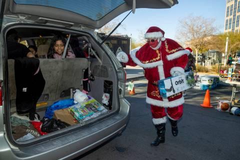 """Santa Claus carga regalos durante el primer evento """"NLVPD Holiday Toy Giveaway"""" en el estaciona ..."""