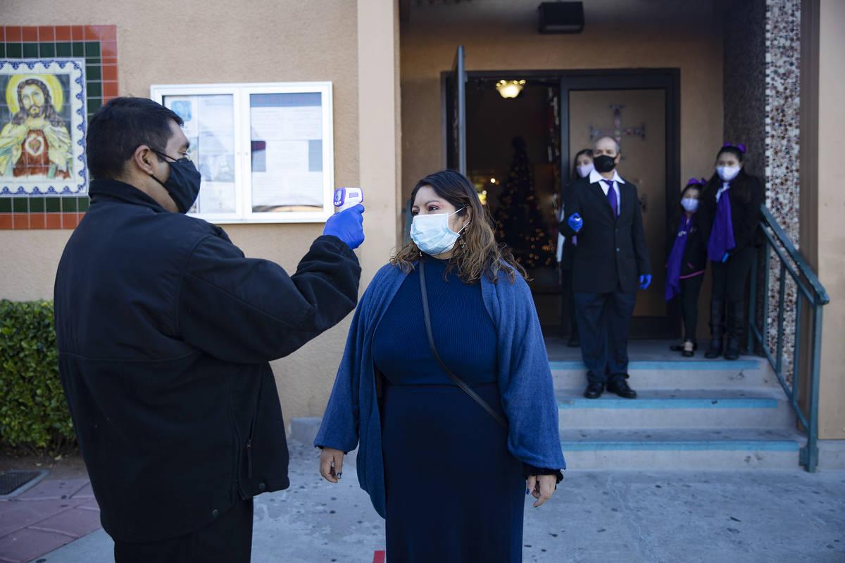 Apolinar Montoya toma la temperatura de Teresa Valentine en St. Anne's Catholic Church en Las V ...