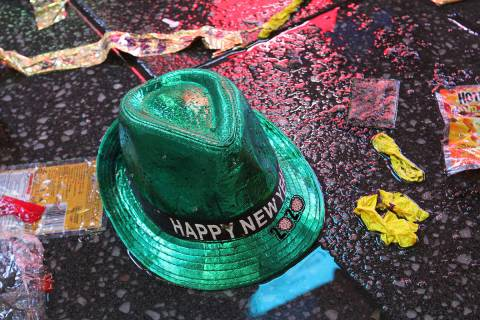"""En esta foto de archivo, un sombrero de """"Feliz Año Nuevo"""" yace en el suelo húmedo junto con o ..."""