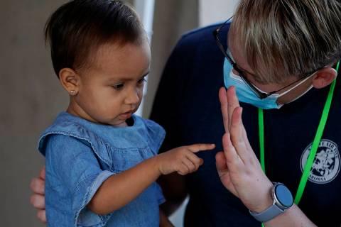 El voluntario Mark McDonald, a la derecha, trabaja con un niño migrante en una clínica habili ...