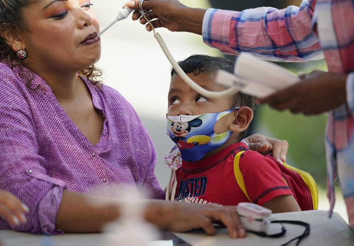 Una mujer que busca asilo en EE.UU. y espera en México, es examinada en una clínica en Matamo ...