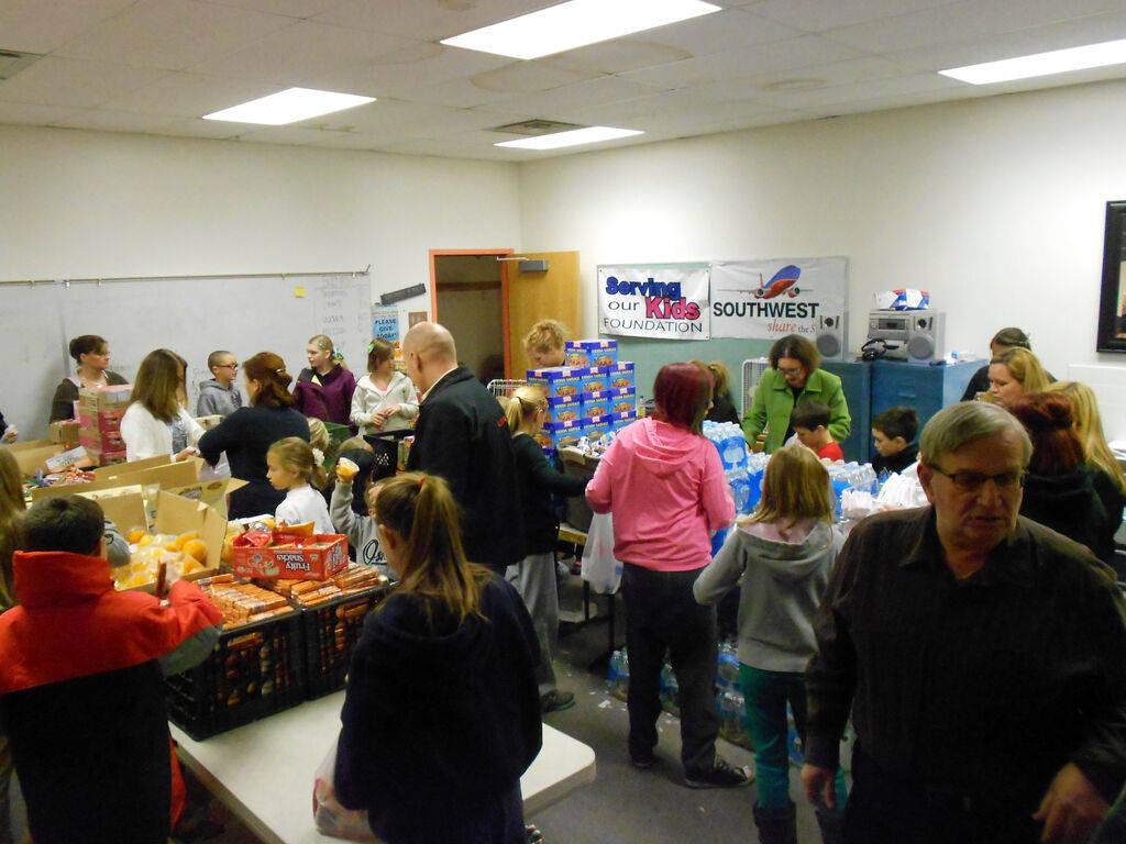 Voluntarios llenan bolsas de comida en el almacén de la Serving Our Kids Foundation. (Linda J. ...
