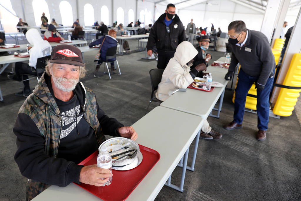 Clientes como Patrick Bailey, de 59 años, comen una comida de Acción de Gracias socialmente d ...