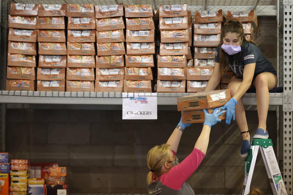 Las voluntarias Grace Ricciardi, de 14 años, y su madre, Sara, de Henderson, reponen los estan ...