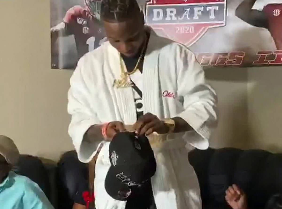 Henry Ruggs III se prepara para ponerse una gorra de los Raiders de Las Vegas después de ser s ...