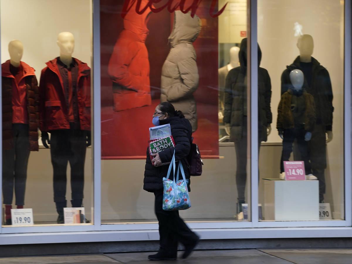 Un peatón usa un cubrebocas al pasar por una vitrina de una tienda de ropa a finales del lunes ...